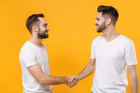 Smiling young men guys friends in white blank empty t-shirts posing isolated on yellow orange background studio portrait. People lifestyle concept. Mock up copy space. Meeting, greeting with hands.