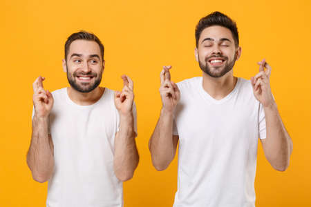 Young men guys friends in white blank t-shirts posing isolated on yellow orange background. People lifestyle concept. Mock up copy space. Wait for special moment, keeping fingers crossed, making wish.