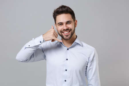 Smiling young unshaven business man in light shirt posing isolated on grey wall background. Achievement career wealth business concept. Mock up copy space. Doing phone gesture like says call me back. Stock fotó