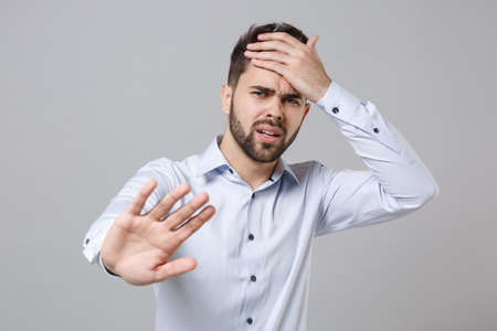 Puzzled young unshaven business man in light shirt posing isolated on grey background. Achievement career wealth business concept. Mock up copy space. Showing stop gesture with palm, put hand on head.