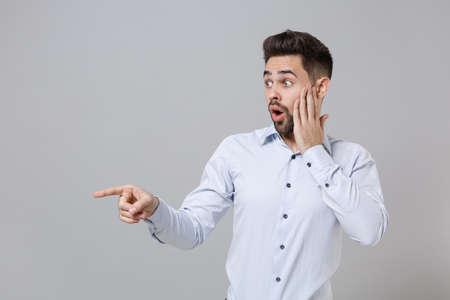 Shocked young unshaven business man in light shirt posing isolated on grey background. Achievement career wealth business concept. Mock up copy space. Pointing index finger aside put hand on cheek. Stockfoto