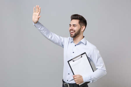 Cheerful business man in light shirt isolated on grey background. Achievement career wealth business concept. Hold clipboard with blank empty sheet workspace waving greet with hand as notices someone. Imagens