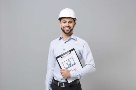 Smiling young unshaven business man in light shirt, protective construction white helmet isolated on grey background. Achievement career wealth business concept. Hold clipboard with papers document. Imagens