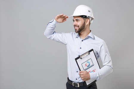 Smiling business man in light shirt protective construction helmet isolated on grey background. Achievement business concept. Hold clipboard with paper document hold hand at forehead looking far away.