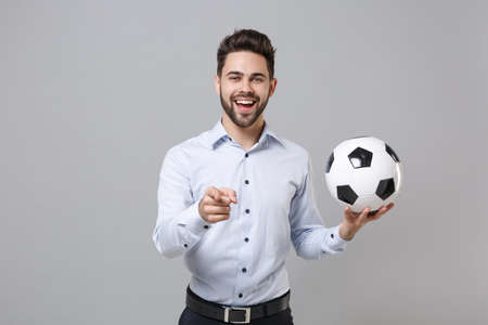 Funny business man football fan in light shirt isolated on grey background. Achievement career sport leisure concept. Cheer up support favorite team with soccer ball pointing index finger on camera.