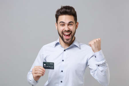 Joyful young unshaven business man in light shirt posing isolated on grey wall background. Achievement career wealth business concept. Mock up copy space. Hold credit bank card doing winner gesture. Imagens