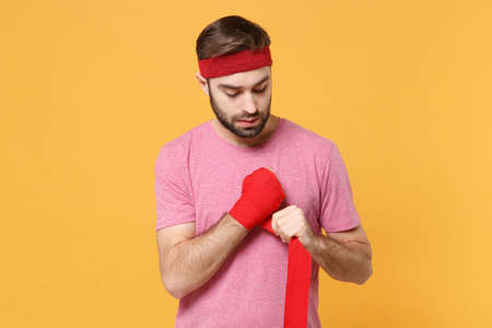 Young bearded fitness sporty guy 20s sportsman in headband t-shirt spend weekend in home gym isolated on yellow wall background. Workout sport motivation concept. Reeling up sports bandages on hand.