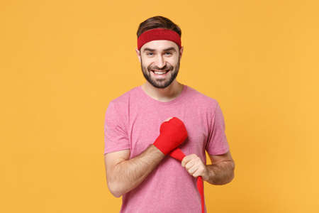 Smiling young bearded fitness sporty guy 20s sportsman in headband t-shirt spend weekend in home gym isolated on yellow background. Workout sport motivation concept. Reeling up sports bandage on hand. 版權商用圖片