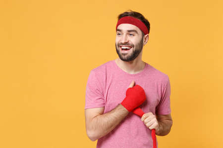 Cheerful bearded fitness sporty guy 20s sportsman in headband t-shirt spend weekend in home gym isolated on yellow background. Workout sport motivation concept. Reeling up sports bandages on hand.