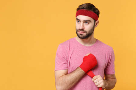 Handsome bearded fitness sporty guy 20s sportsman in headband t-shirt spend weekend in home gym isolated on yellow background. Workout sport motivation concept. Reeling up sports bandages on hand.
