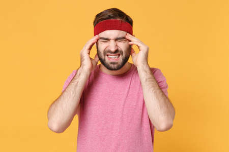 Tired sick fitness sporty guy 20s sportsman in headband t-shirt spend weekend in home gym isolated on yellow background. Workout sport motivation lifestyle concept. Put hands on head, having headache. 免版税图像