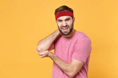 Displeased young bearded fitness sporty guy 20s sportsman in headband t-shirt spend weekend in home gym isolated on yellow background. Workout sport motivation concept. Touching arm elbow get injured.