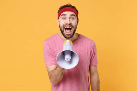 Excited young bearded fitness sporty guy 20s sportsman in headband t-shirt spend weekend in home gym isolated on yellow background. Workout sport motivation concept. Scream in megaphone looking aside.