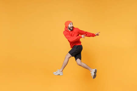 Excited young bearded fitness sporty guy 20s sportsman in hat hoodie shorts in home gym isolated on yellow background. Workout sport motivation lifestyle concept. Jumping pointing index fingers aside. Stock Photo
