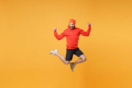 Screaming bearded fitness sporty guy sportsman in hat, hoodie, shorts spend weekend in home gym isolated on yellow background. Workout sport motivation concept. Jumping doing exercise with dumbbell. Stock Photo