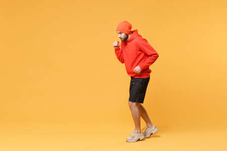 Side view of young bearded fitness sporty guy sportsman in hat, hoodie, shorts spend weekend in home gym isolated on yellow background in studio. Workout sport motivation lifestyle concept. Running.