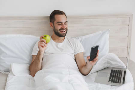 Calm young handsome bearded man lying in bed with white sheet pillow blanket in bedroom at home. Male spending time in room, eat green apple. Rest relax good mood lifestyle concept. Mock up copy space