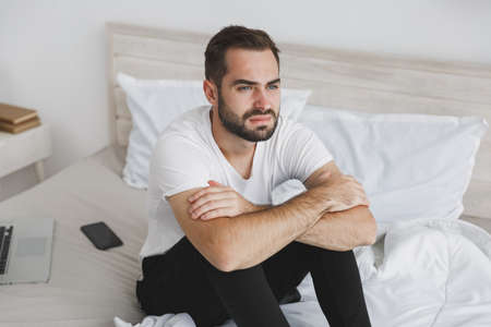 Calm young handsome bearded man sitting in bed with white sheet pillow blanket in bedroom at home. Sad upset male spending time in room. Rest relax good mood lifestyle concept. Mock up copy space. Imagens