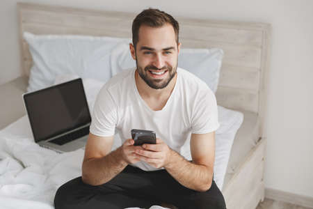 Young bearded man sits in bed with white sheet pillow blanket in bedroom at home. Male spending time in room using mobile phone, display pc. Rest relax good mood lifestyle concept. Mock up copy space.