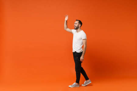 Side view of cheerful young man in casual white t-shirt posing isolated on orange background in studio. People lifestyle concept. Mock up copy space. Waving and greeting with hand as notices someone.