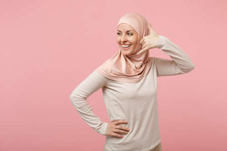 Smiling young arabian muslim woman in hijab light clothes posing isolated on pink background. People religious Islam lifestyle concept. Mock up copy space. Doing phone gesture like says call me back.