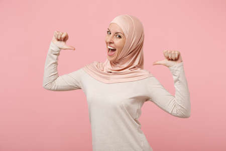 Smiling young arabian muslim woman in hijab light clothes posing isolated on pink background studio portrait. People religious Islam lifestyle concept. Mock up copy space. Pointing thumbs on herself. Stockfoto