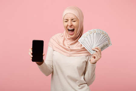 Happy arabian muslim woman in hijab light clothes posing isolated on pink background. People religious lifestyle concept. Mock up copy space. Hold cellphone with blank empty screen, fan of cash money.