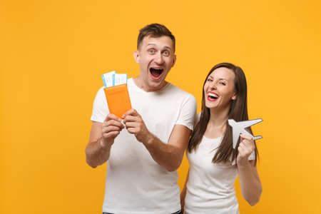 Cheerful young couple two friends in white t-shirts posing isolated on yellow orange background. People lifestyle concept. Mock up copy space. Holding passport tickets boarding pass, paper airplane.