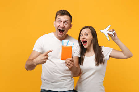 Excited young couple two friends in white t-shirts posing isolated on yellow orange background. People lifestyle concept. Mock up copy space. Holding passport tickets boarding pass, paper airplane.