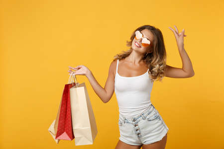 Funny young woman girl in eyeglasses posing isolated on yellow orange background. People lifestyle concept. Mock up copy space. Hold package bag with purchases after shopping, showing victory sign.