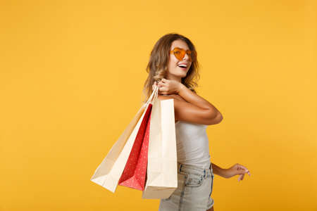 Side view of laughing young woman girl in eyeglasses posing isolated on yellow orange wall background. People lifestyle concept. Mock up copy space. Holding package bag with purchases after shopping. 免版税图像