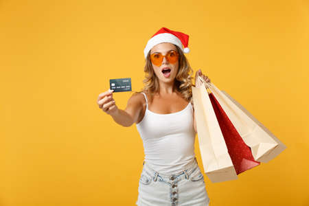 Shocked Santa girl in Christmas hat glasses posing isolated on yellow background. Happy New Year 2020 celebration holiday concept. Mock up copy space. Hold package bag after shopping credit bank card.