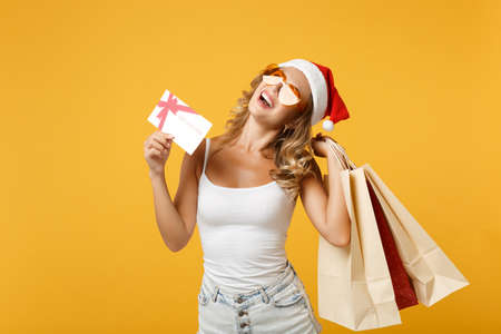 Funny Santa girl in Christmas hat, glasses posing isolated on yellow background. Happy New Year 2020 celebration holiday concept. Mock up copy space. Hold package bag after shopping, gift certificate.