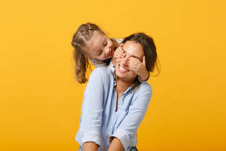 Woman in light clothes have fun with cute child baby girl 4-5 years old. Mommy little kid daughter isolated on yellow background studio portrait. Mothers Day love family parenthood childhood concept.