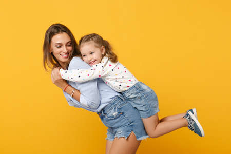 Woman in light clothes have fun with cute child baby girl 4-5 years old. Mommy little kid daughter isolated on yellow background studio portrait. Mothers Day love family parenthood childhood concept. Banque d'images