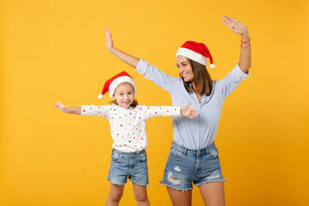 Woman child baby girl 4-5 years old in Christmas Santa hat. Mommy little kid daughter isolated on yellow background studio portrait. Happy New Year 2020 celebration holiday concept. Mock up copy space