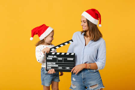 Woman child girl in Christmas Santa hat hold clapperboard. Mommy little kid daughter isolated on yellow background studio portrait. Happy New Year 2020 celebration holiday concept. Mock up copy space.