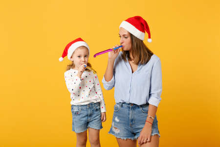 Woman child baby girl in Christmas Santa hat blow in pipe. Mommy little kid daughter isolated on yellow background studio portrait. Happy New Year 2020 celebration holiday concept. Mock up copy space.