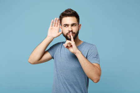 Young man in casual clothes posing isolated on blue wall background, studio portrait. People lifestyle concept. Mock up copy space. Say hush be quiet with finger on lips shhh gesture, try to hear you. 免版税图像