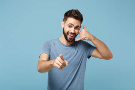 Young smiling man in casual clothes posing isolated on blue wall background. People lifestyle concept. Mock up copy space. Doing phone gesture like says call me back, pointing index finger on camera. Stock fotó