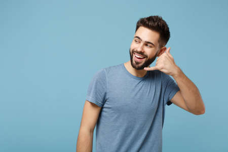 Young cheerful attractive man in casual clothes posing isolated on blue background in studio. People lifestyle concept. Mock up copy space. Doing phone gesture like says call me back, looking aside.