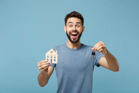 Young surprised man in casual clothes posing isolated on blue wall background, studio portrait. People sincere emotions lifestyle concept. Mock up copy space. Holding in hands house and bunch of keys. Stock Photo