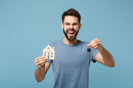 Young overjoyed man in casual clothes posing isolated on blue wall background, studio portrait. People sincere emotions lifestyle concept. Mock up copy space. Holding in hands house and bunch of keys.