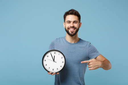 Young smiling attractive man in casual clothes posing isolated on blue wall background, studio portrait. People lifestyle concept. Mock up copy space. Holding in hands, pointing index finger on clock.