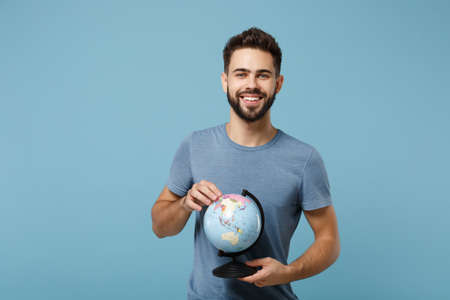 Young smiling handsome man in casual clothes posing isolated on blue wall background, studio portrait. People sincere emotions lifestyle concept. Mock up copy space. Holding in hands world globe. Stock fotó