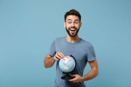 Young excited cheerful man in casual clothes posing isolated on blue wall background, studio portrait. People sincere emotions lifestyle concept. Mock up copy space. Holding in hands world globe.