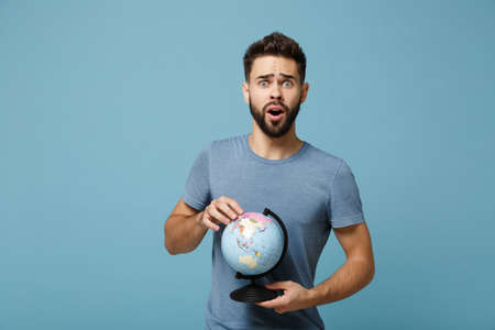 Young shocked bewildered man in casual clothes posing isolated on blue wall background, studio portrait. People sincere emotions lifestyle concept. Mock up copy space. Holding in hands world globe.