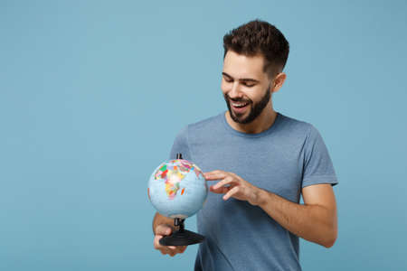 Young cheerful man in casual clothes posing isolated on blue wall background, studio portrait. People lifestyle concept. Mock up copy space. Holding in hands, pointing index finger on world globe.