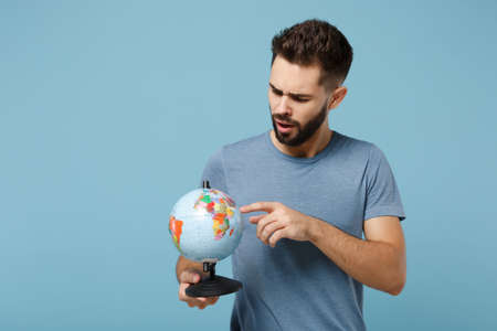 Young preoccupied man in casual clothes posing isolated on blue wall background, studio portrait. People lifestyle concept. Mock up copy space. Holding in hands, pointing index finger on world globe. Stock fotó