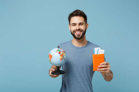 Young smiling man in casual clothes posing isolated on blue wall background in studio. People lifestyle concept. Mock up copy space. Holding in hands world globe, passport, boarding pass tickets. Stock fotó